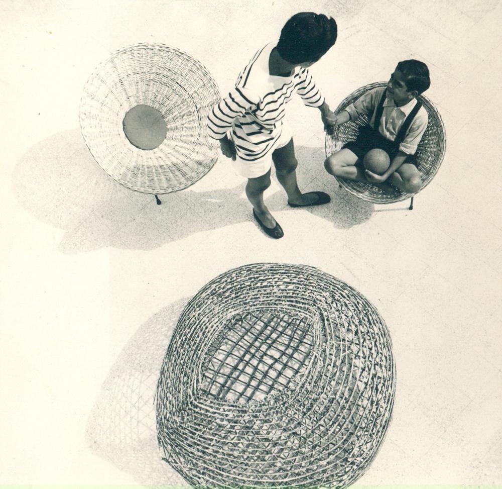 """Roberto Mango. Seduta a cono in vimini sul terrazzo della sua casa di Positano accanto alla """"nassa"""" da pesca, dalla cui strategia costruttiva e impiego di materiale trae fondamento. Foto R.Mango/Archivio Mango."""